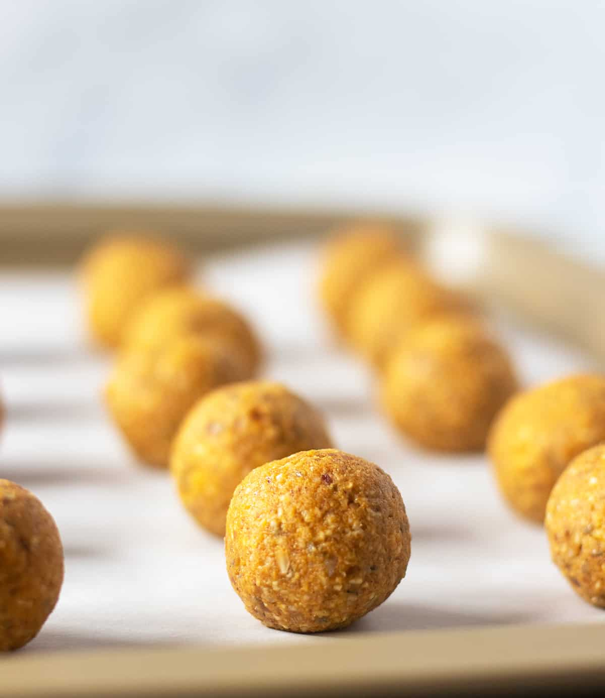 pumpkin pie date energy balls on a parchment lined tray