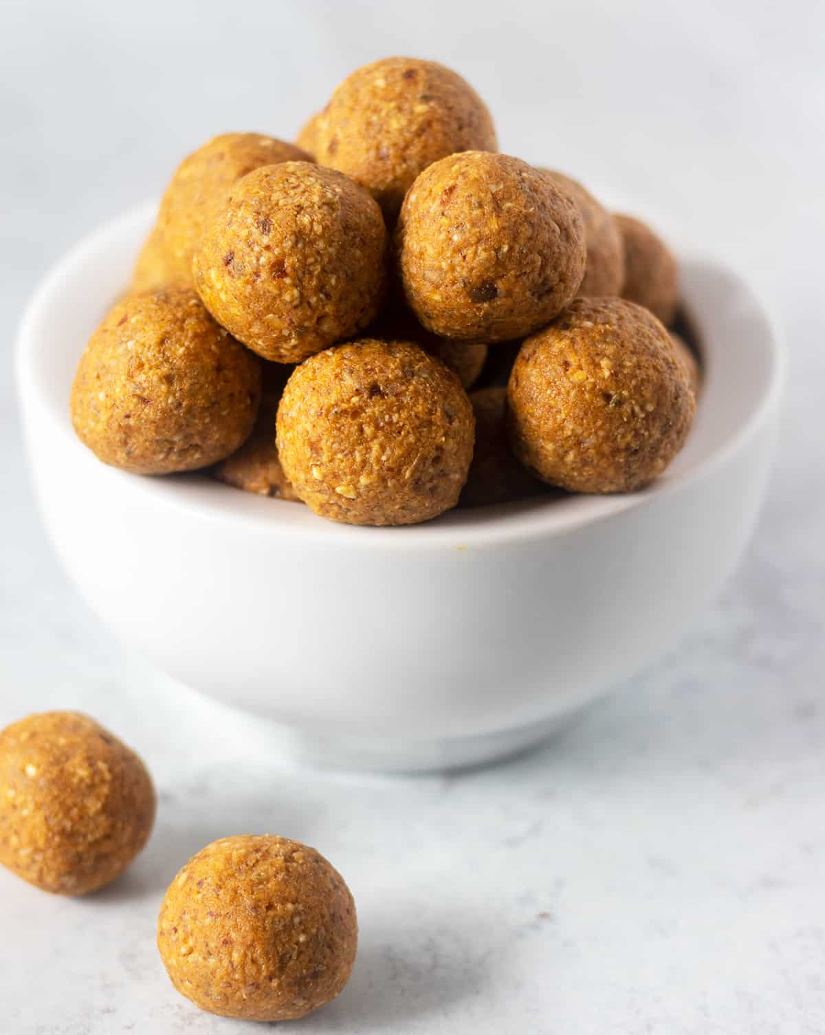 pumpkin pie date energy balls in a white bowl stacked