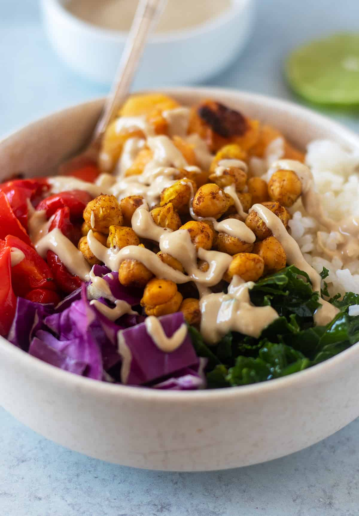 buddha bowl in a white bowl with silver spoon that's topped with tahini sauce