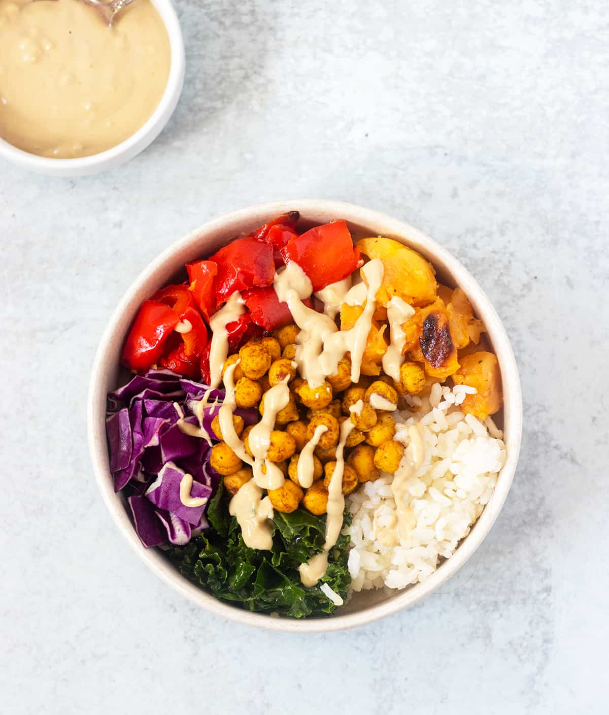 buddha bowl drizzled with tahini sauce and a bowl of tahini sauce in the background