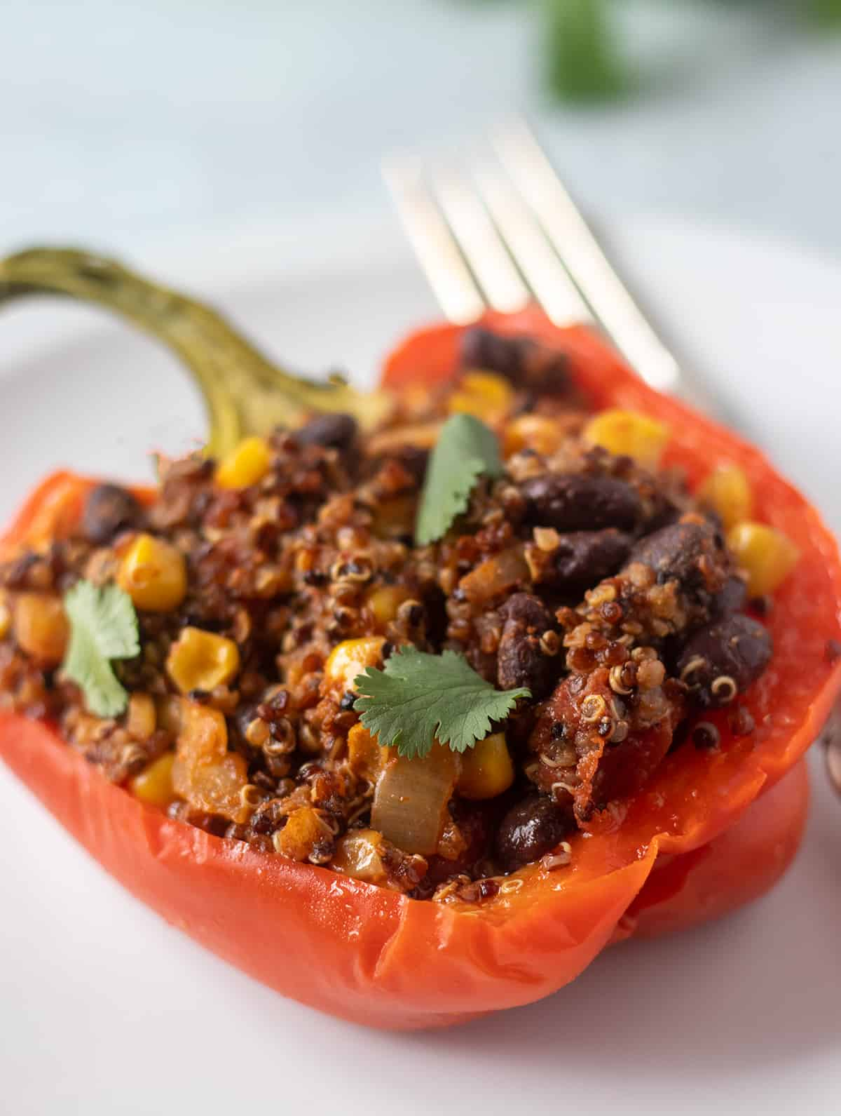 stuffed red bell pepper on white plate with silver fork