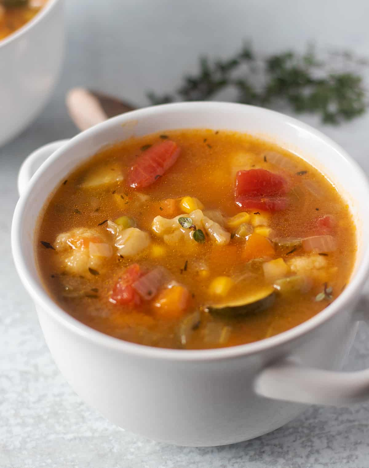 easy vegetable soup in a white bowl with fresh thyme in the background
