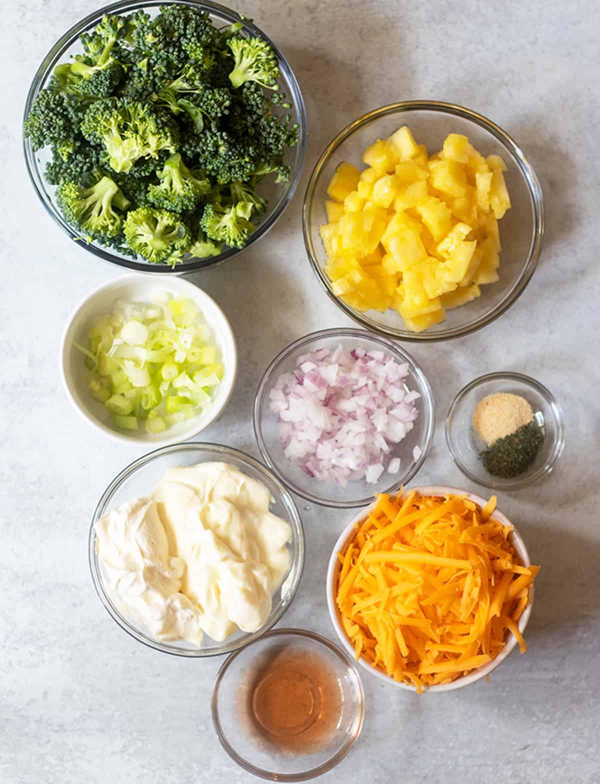 broccoli florets, diced pineapple, red onion, mayo, seasonings, shredded cheddar cheese, green onions, vingegar