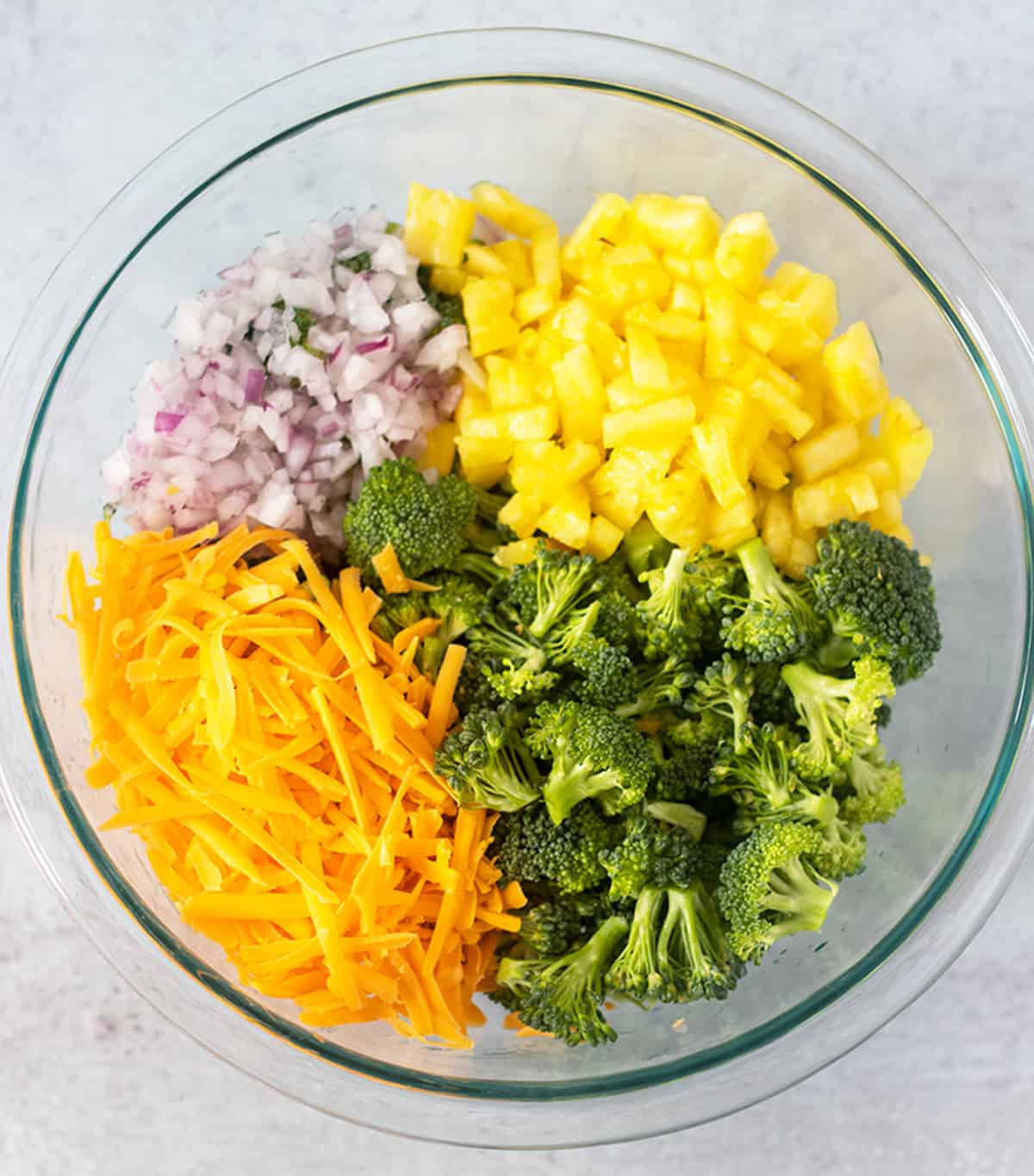 broccoli florets, diced pineapple, red onion and cheddar cheese in a clear mixing bowl.