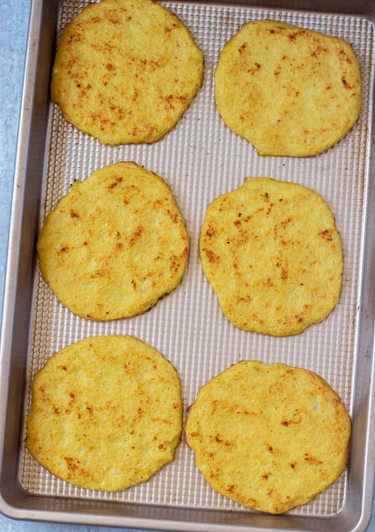 cauliflower tortillas on a gold baking pan after cooking.