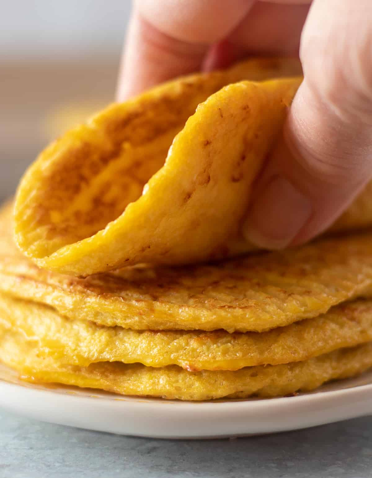 Cauliflower tortillas stacked on a plate with a hand grabbing and bending one.