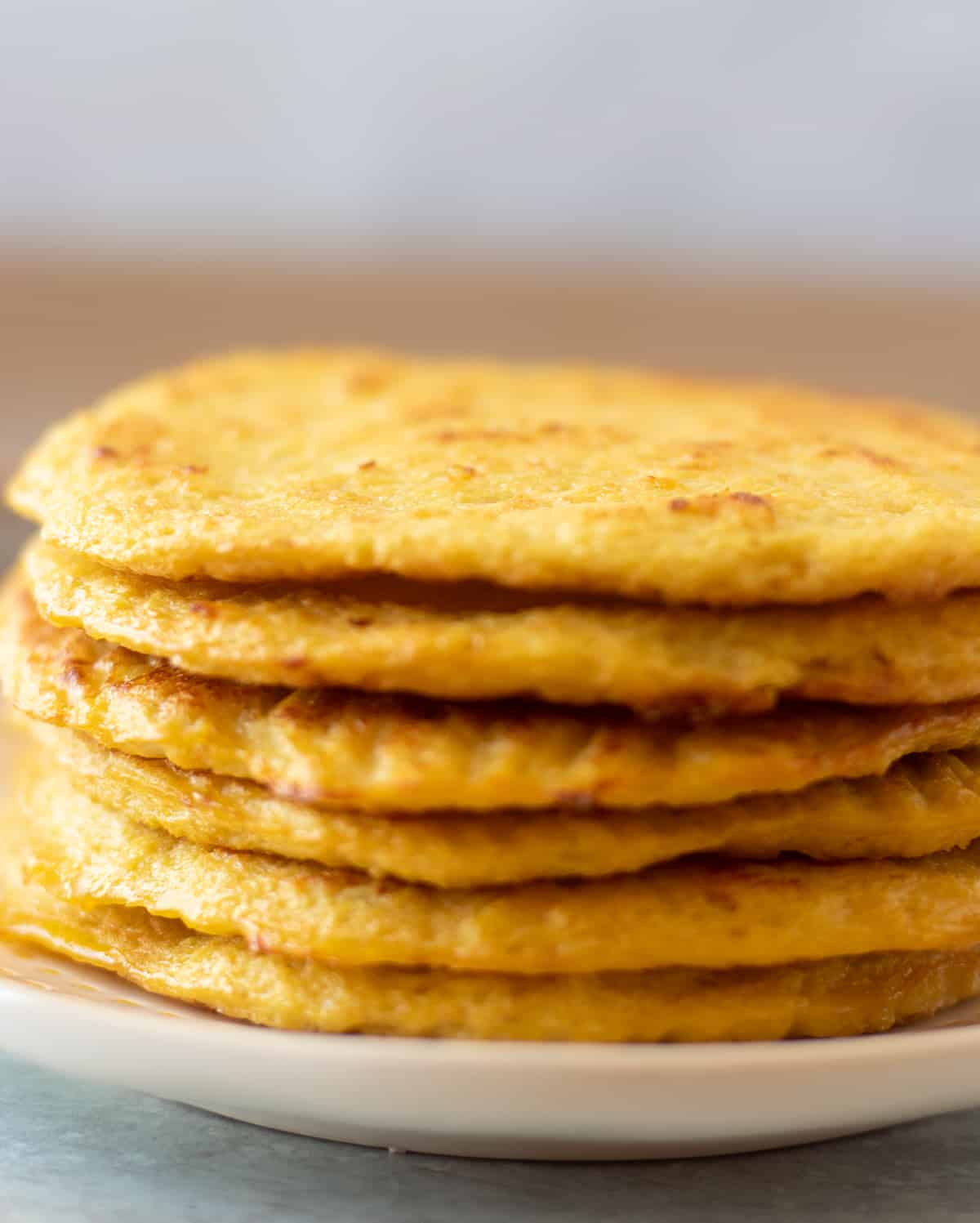 cauliflower tortillas stacked on a white plate with yellow trim