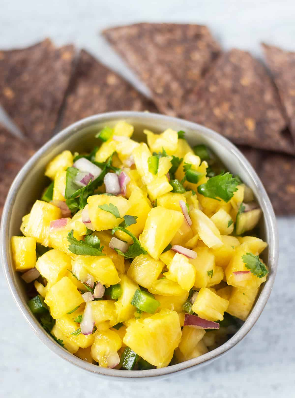 pineapple salsa in a grey bowl with blue tortilla chips beside the bowl for serving.
