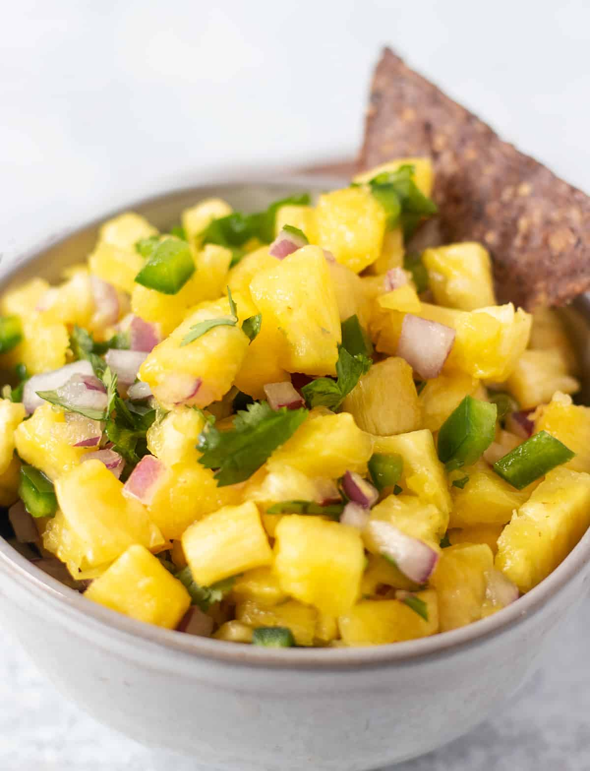 pineapple salsa in a grey bowl with a black bean tortilla chip in the bowl for dipping.