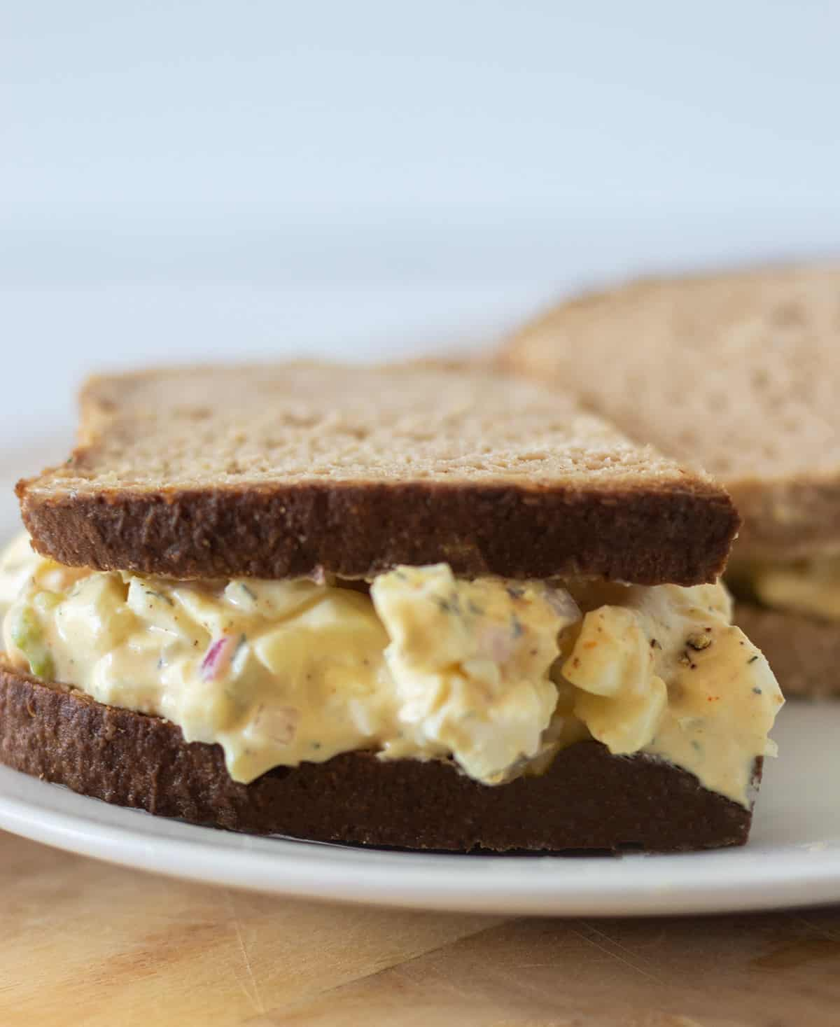 egg salad on a sandwich served on a white plate