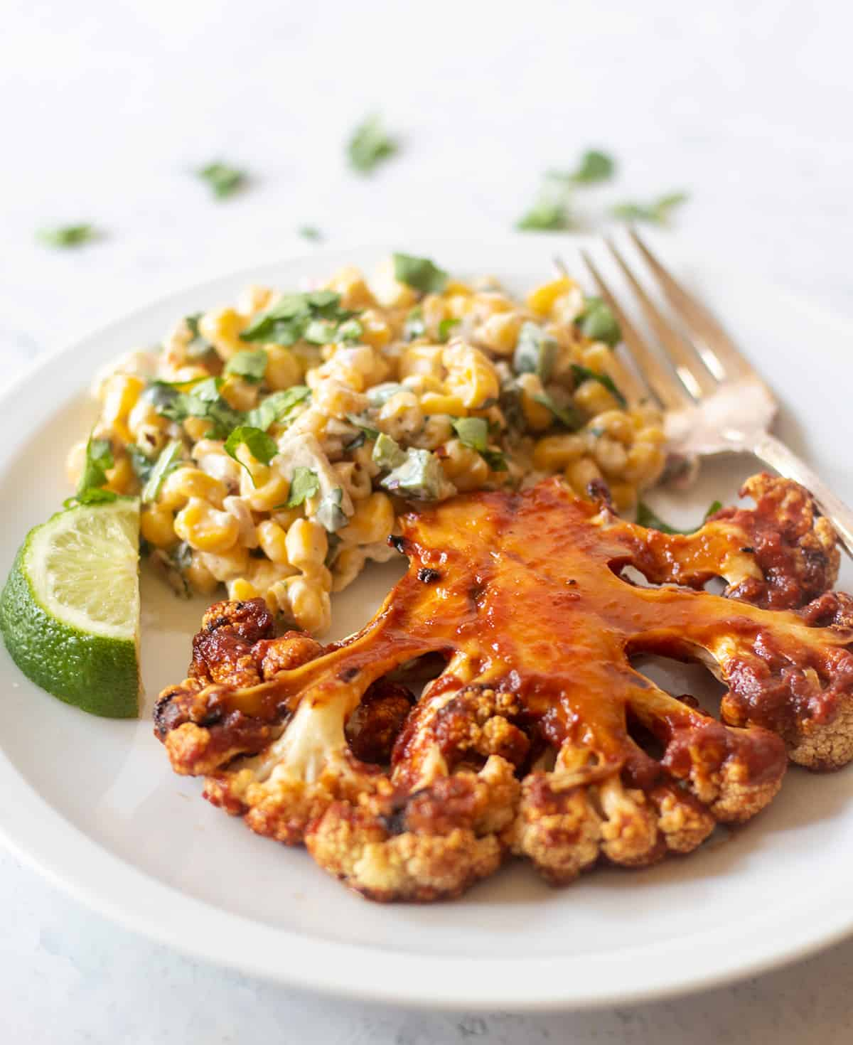 Grilled cauliflower steak with barbecue sauce on a white plate with a side of mexican street corn salad and a lime wedge. A silver fork on the plate for serving.