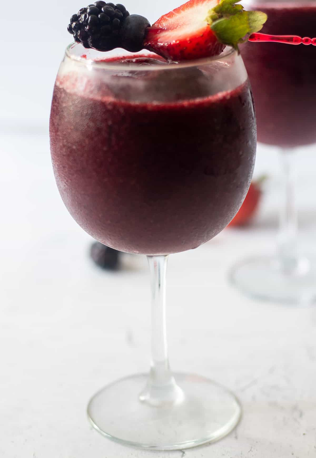 berry wine slushie in a clear wine glass with a toothpick with a half of a fresh strawberry, fresh blackberry and fresh blueberry on it.