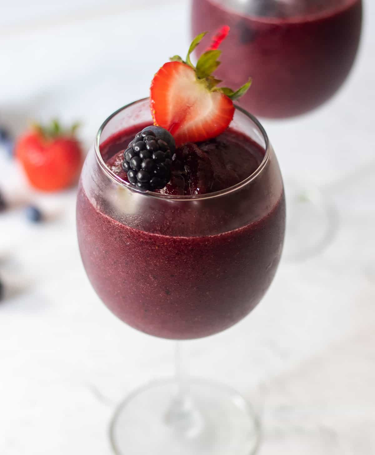 berry wine slushie in a clear wine glass with fresh fruit on top