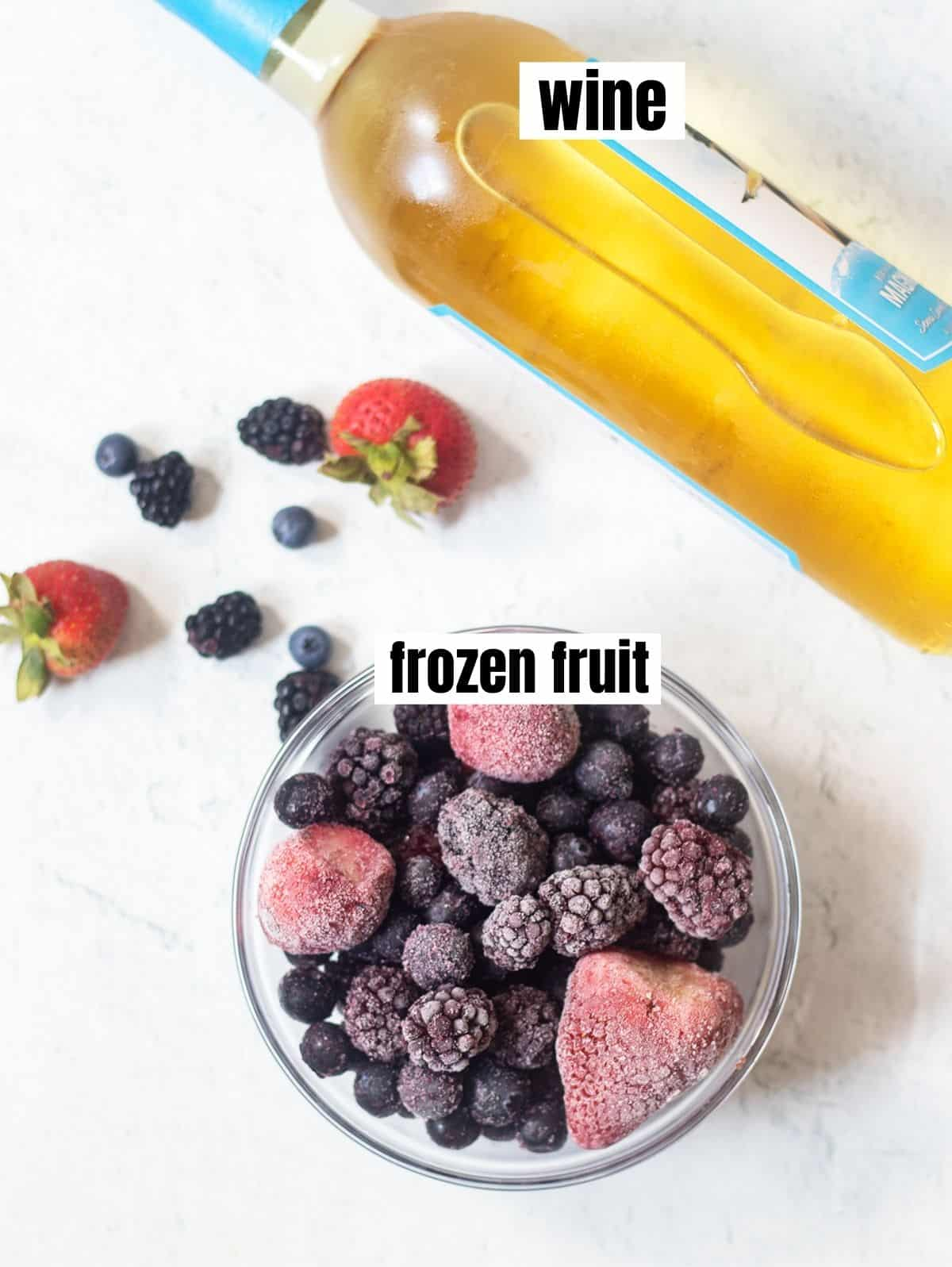 bottle of white wine and a blend of frozen blackberries, blueberries and strawberries in a bowl. Some fresh strawberries, blueberries and blackberries in the background.