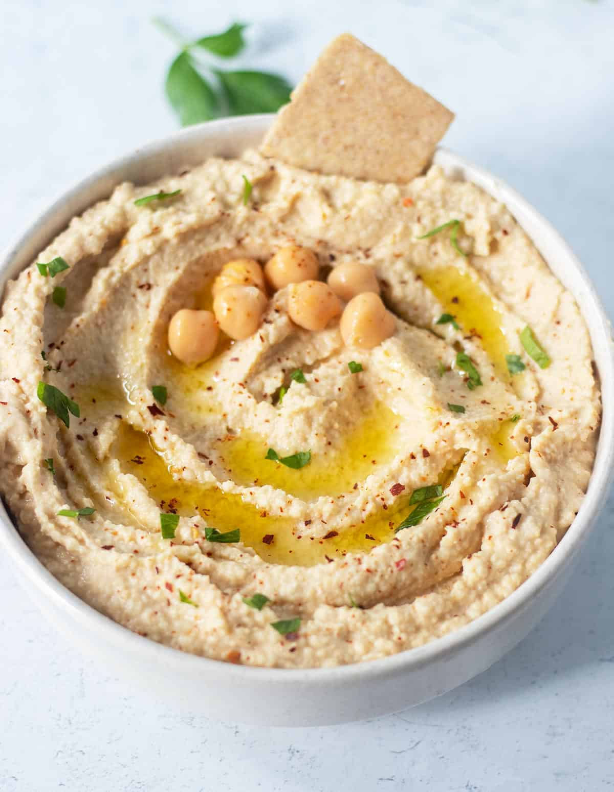 roasted garlic hummus in a white bowl garnished with olive oil, chickpeas, fresh chopped parsley and red chili pepper flakes. A cracker in the bowl for dipping.