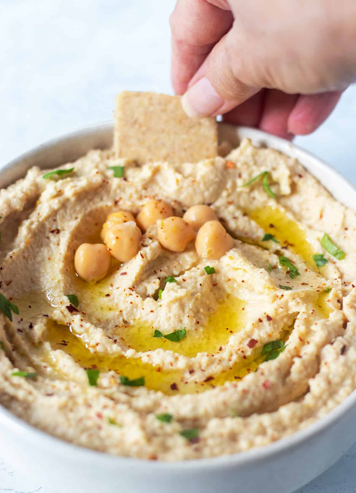 roasted garlic hummus in a white bowl garnished with olive oil, chickpeas, chopped parsley and red chili pepper flakes. A hand reaching in the dip with a cracker.