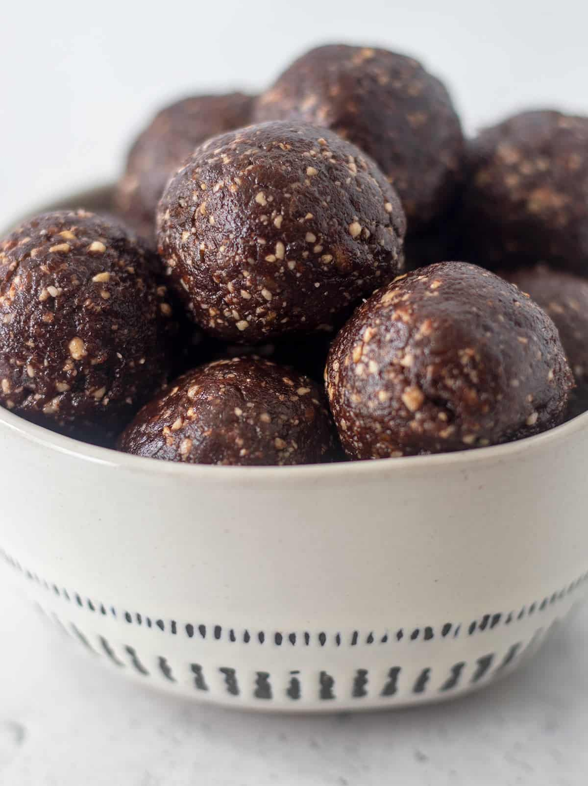 chocolate protein balls in a white bowl with blue trim.