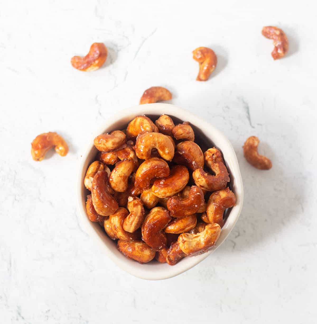 Honey roasted cashews in a white bowl with some of the cashews beside the bowl.