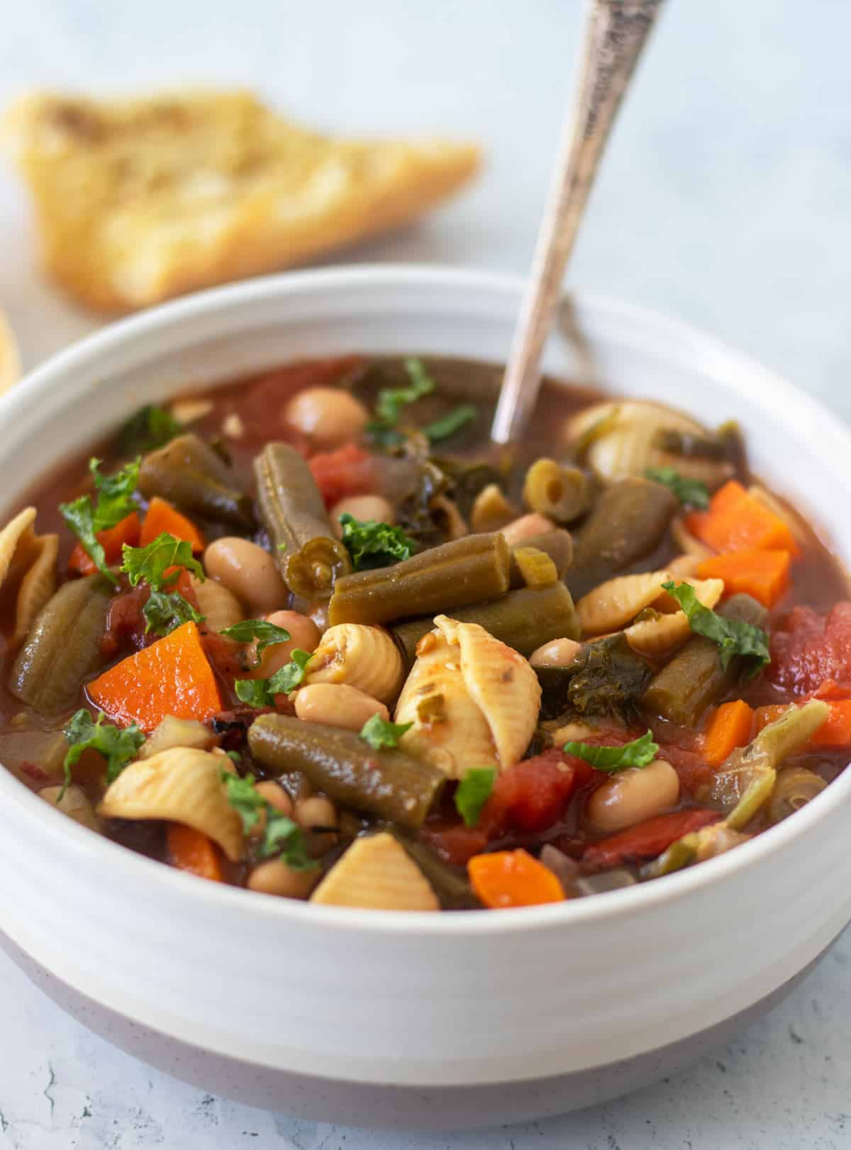 vegetarian minestrone soup in a white and grey bowl with a silver spoon. A slice of garlic bread in the background.